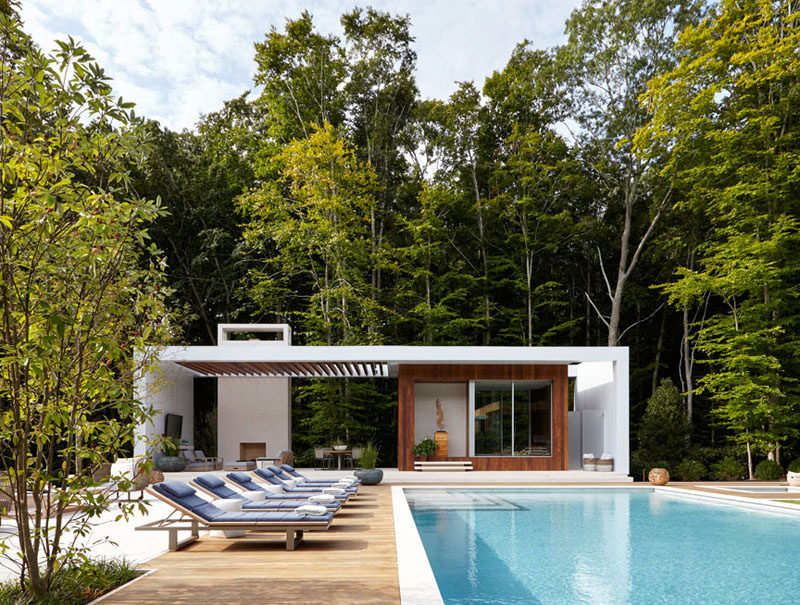 This white and wood pool house features a covered outdoor lounge area with a fire place. Blue upholstered sun chairs line the length of the pool.