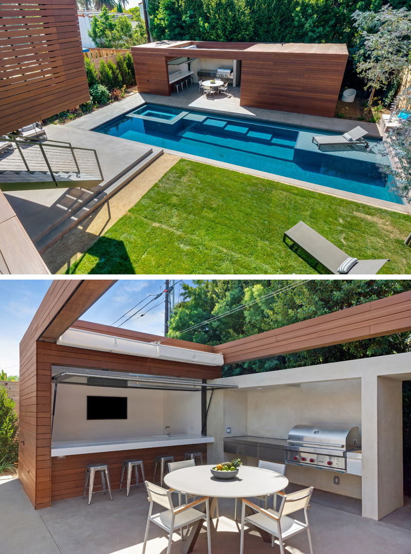 This modern wood and concrete pool house features a bar area with a TV, and a full sized BBQ. A skylight above makes this the perfect place to snack beside the pool.