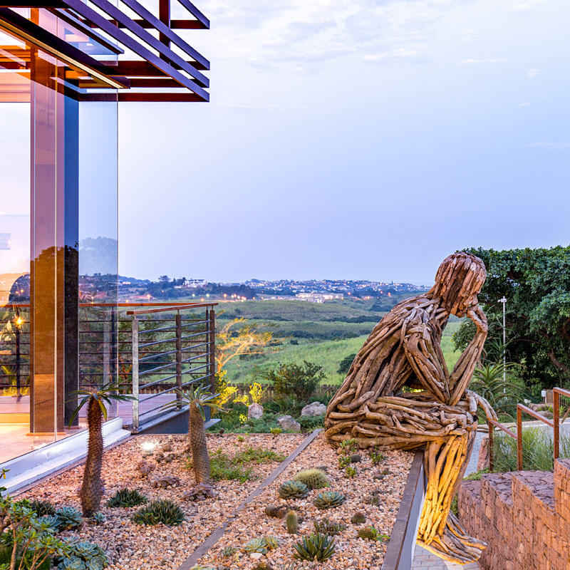 Another large wood art installation, the thinking man, sits in front of a mini rock garden and looks out over the side of this modern house.