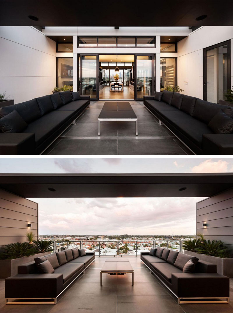 This modern outdoor balcony has an unobstructed view of the city. Two large black sofas provide more than enough room for guests.
