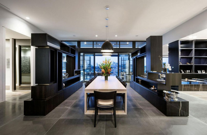 Inside this modern penthouse, a large white dining table sits below three black pendant lights, and divides different areas of the home.