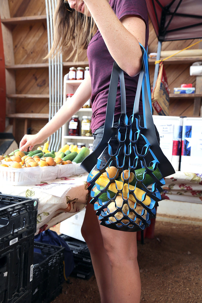 This modern black and blue reusable plastic bag is easy to carry, and expands to fit various contents.