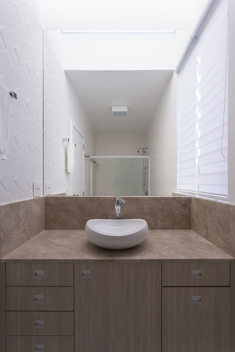 In this modern bathroom, a decorative white tile on the wall adds texture, while the large mirror helps to make the small space appear larger than it is.