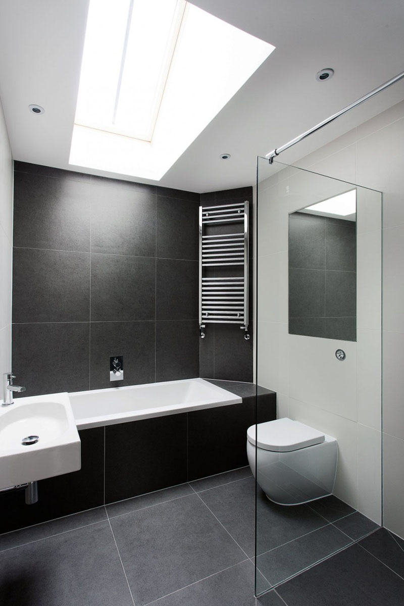 In this modern bathroom, a skylight shines light on to the large dark grey tiles used throughout, and a glass wall separates the shower area from the rest of room.