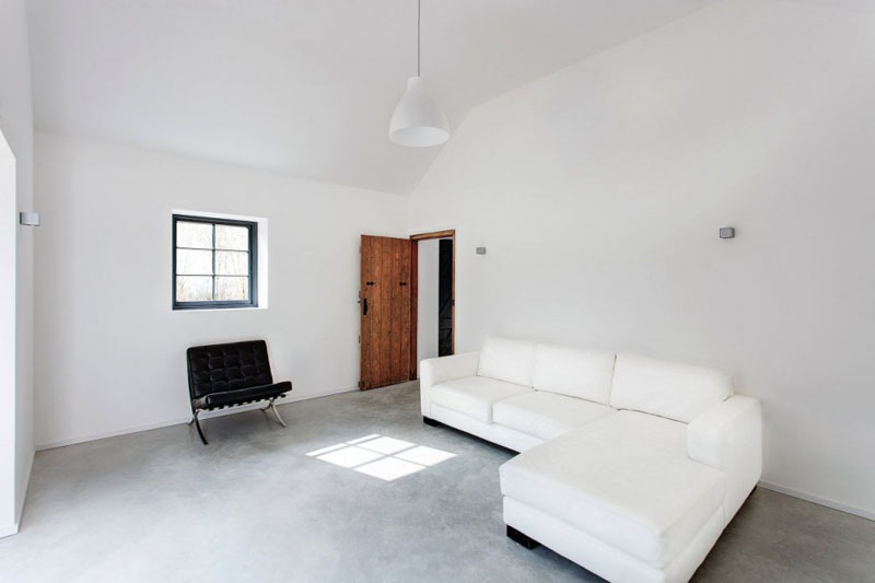 This modern living room is full of open space and is minimally decorated. The smooth concrete floor, white pendant light, and the white and black furniture keeps this space simple.