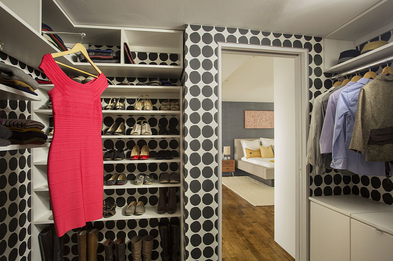 This modern master bedroom has a walk-in closet, with circular patterned black and white wallpaper that stands out among the white built-in shelves and racks.