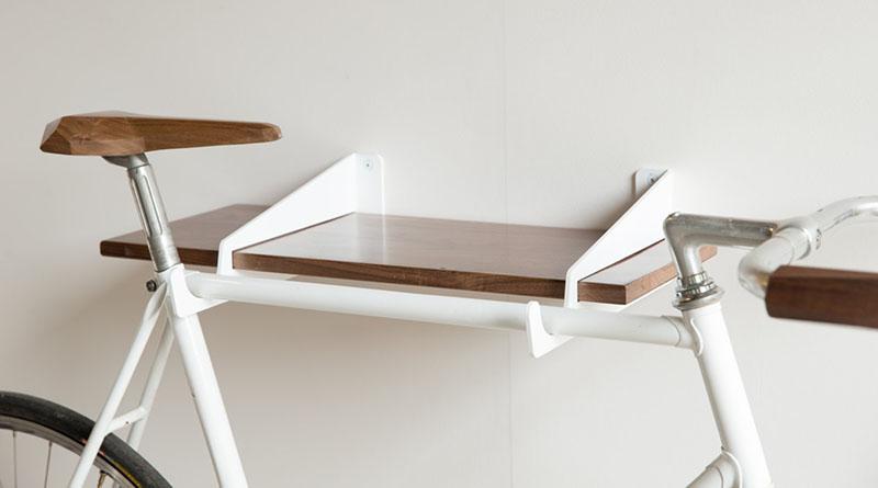 A modern white and wood shelf that doubles as a wall mounted bike rack.