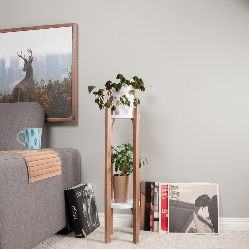 This modern walnut wood plant stand is two tiered with white shelves to hold multiple plants.