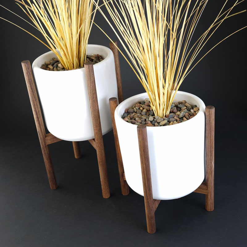 Cylinder shaped white ceramic pots sit inside these staggered walnut wood plant stands. Mid-century inspired, these modern plants stands would suit for any home decor.