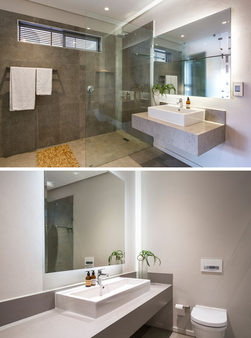 The large shower in this modern bathroom is defined by the stone tiles and glass shower surround. Next to the shower is a floating vanity and backlit rectangular mirror. Off to the side, a separate space is provided for the the toilet.
