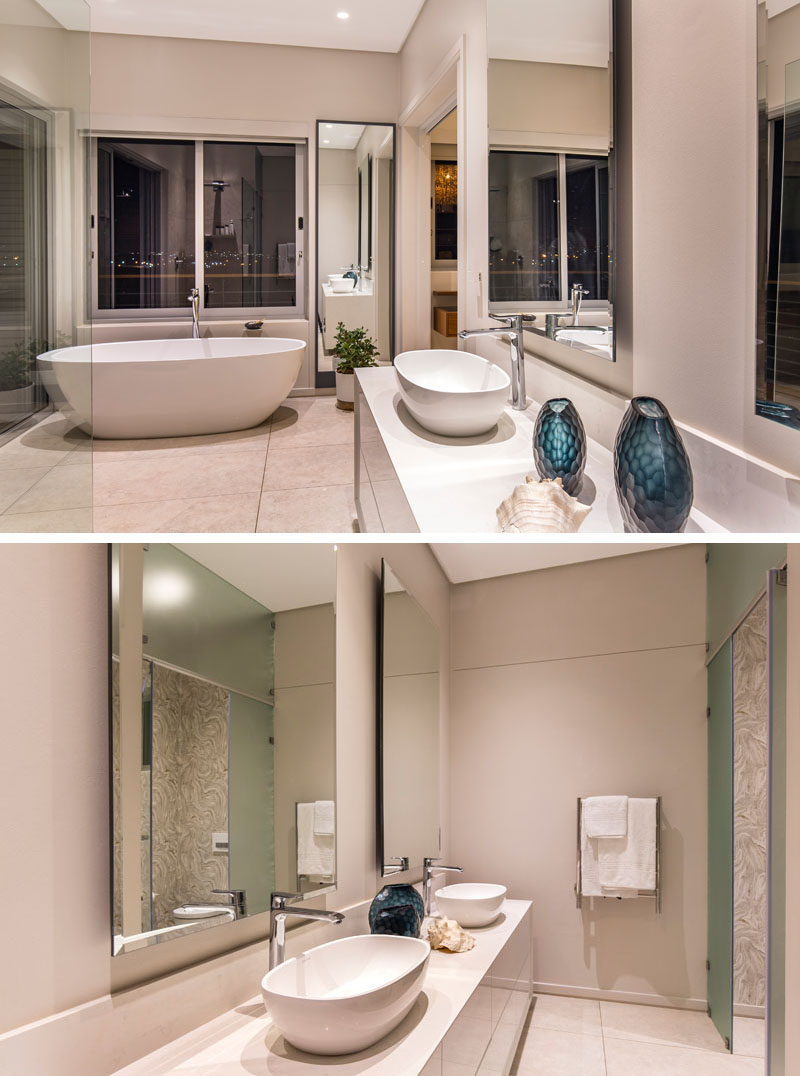 In this modern master bathroom, a white standalone tub is placed beside a large window providing a view of the city. In front of the glass shower, his and her sinks sit on top of the white counter.