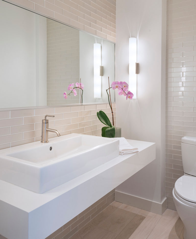Light pink rectangular tiles cover the walls in this modern bathroom that also has light wood flooring, while a floating white vanity sits below a large mirror.