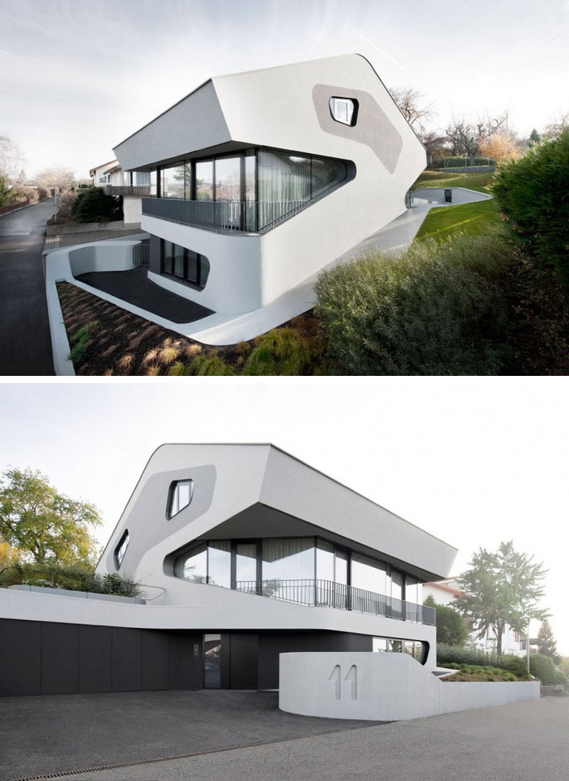 This modern house is white with touches of grey and black, and has curved features throughout.