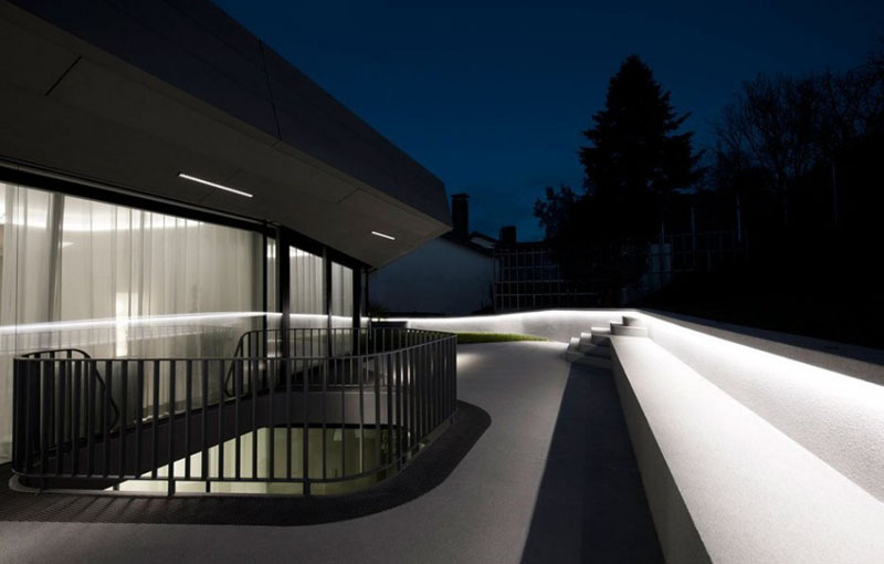 This modern house has a balcony with hidden lighting that lines the white railing, providing light and safety.