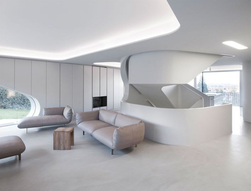 Arriving to the second level of the house, the recessed ceiling in this modern living room has hidden lighting making this white room even brighter. Light colored upholstered furniture, and a small wood coffee table sits comfortably on the bare concrete floor.