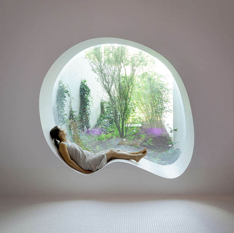 Perfect for daydreaming, this modern white curved window seat looks out over a tranquil garden.