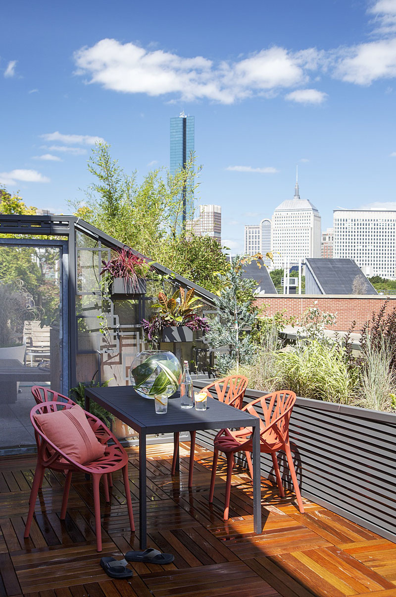 This modern wood balcony is furnished with a black table, and bright orange chairs. The potted plants in this space don't interfere with the spectacular view of the city.