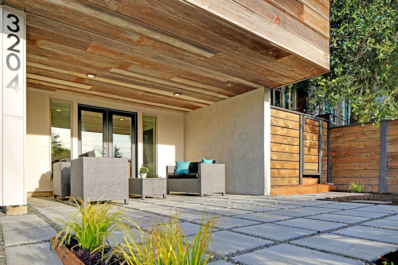 Beside the front door, this modern house cantilevers out creating a perfect covered patio spot. Smooth cement pavers ensure it's easy enough to walk around without shoes.