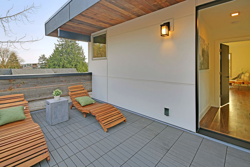 At the top of this modern house is a private sun deck with two wood sun chairs.