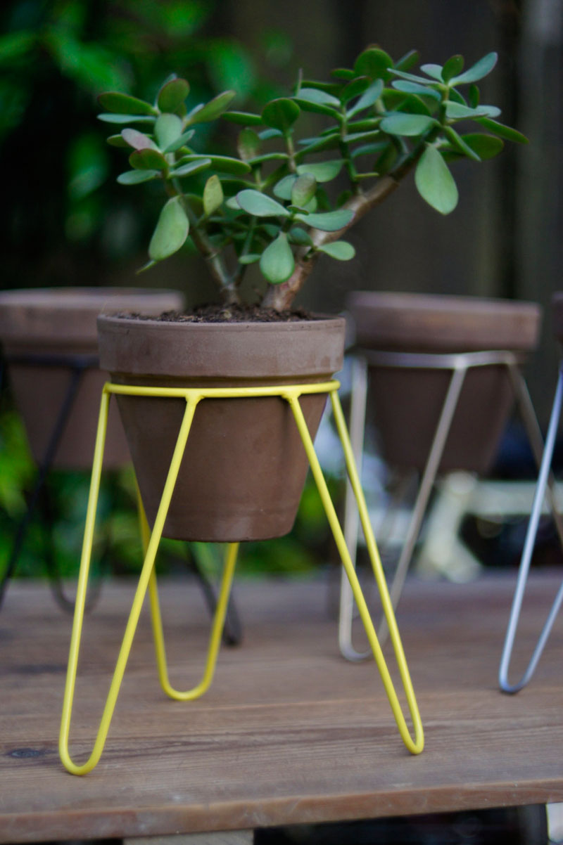 Modern in design and small in size, this yellow steel tripod plant stand is perfect for small plants and herbs.
