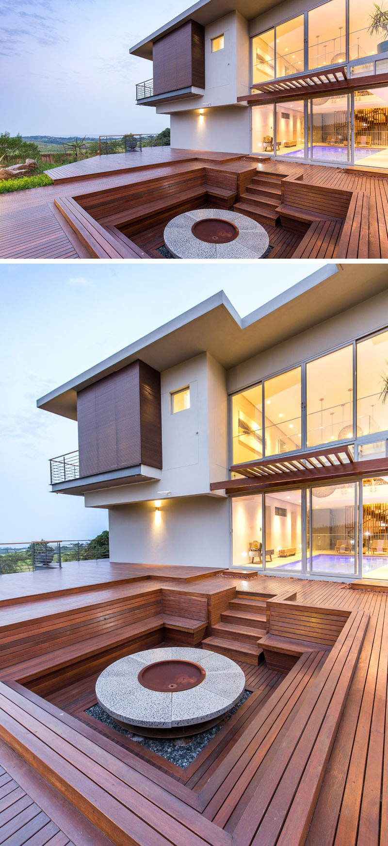 This modern house has a large wood deck that's home to a sunken wood firepit with built-in benches, ideal for outdoor entertaining and star gazing.