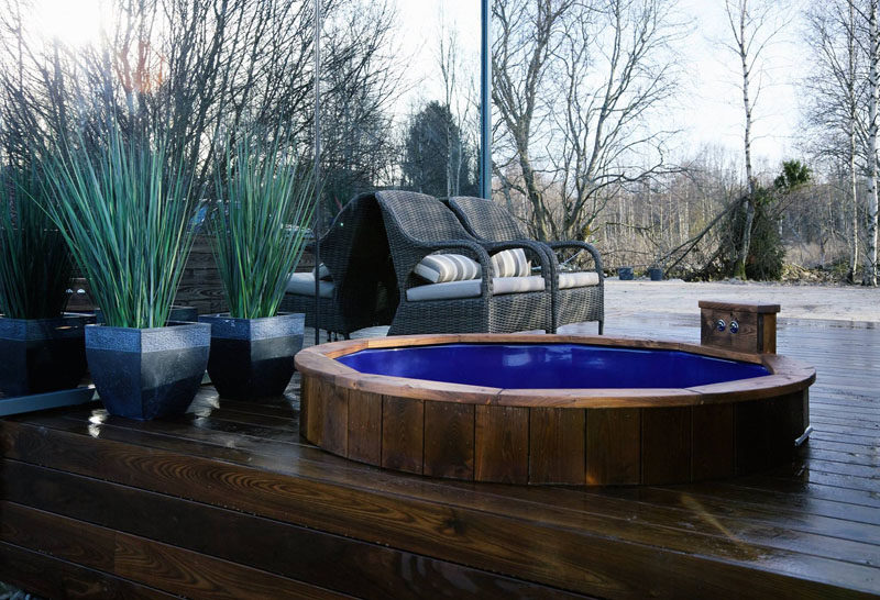 Out on this modern wood deck, there is a built-in hot tub to jump into while enjoying the outdoors.