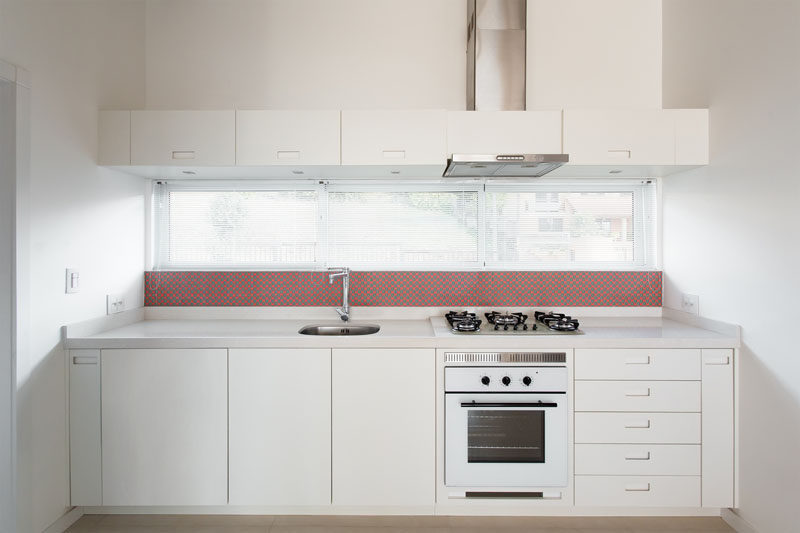 In this small kitchen, simple white cabinets almost blend in with the white walls, while the backsplash provides a dash of red.