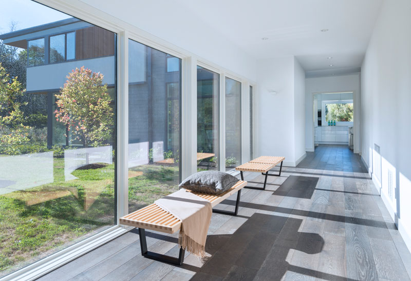 Going inside this modern house, two wood benches are placed in front of large windows that line a long white hallway with dark wood flooring.
