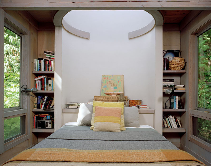 This bedroom inside a modern cabin features built-in shelving and windows on either side of the bed.