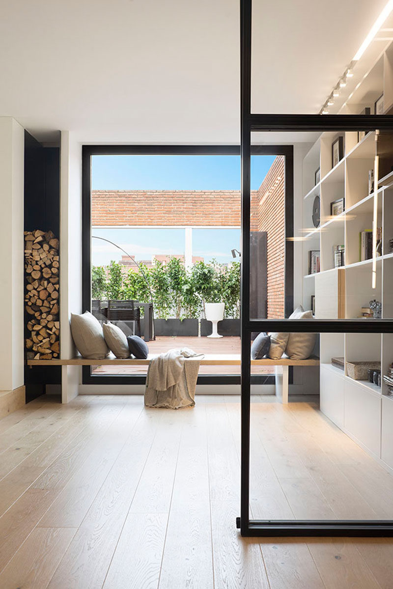 A built-in wood window seat sits between the shelving unit and the firewood storage in this modern penthouse, while the large window provides plenty of natural light and views of the outdoor space.