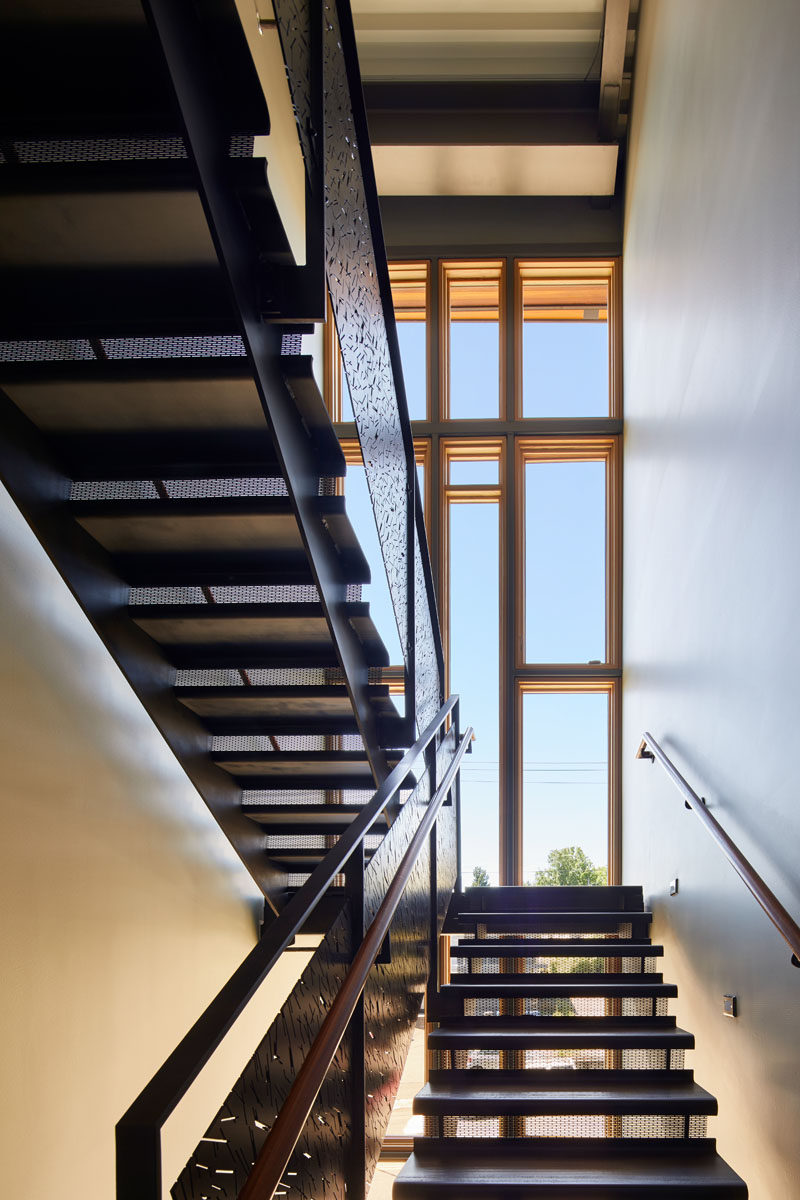 The stairwell has a three-story glass wall that fills the space with natural light.