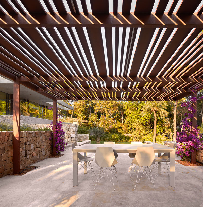 This modern house in Spain has an alfresco dining area that sits beneath a pergola.