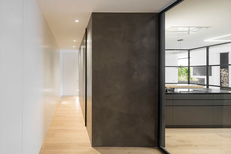 A powder room is hidden within a dark box in the hallway of this modern penthouse.