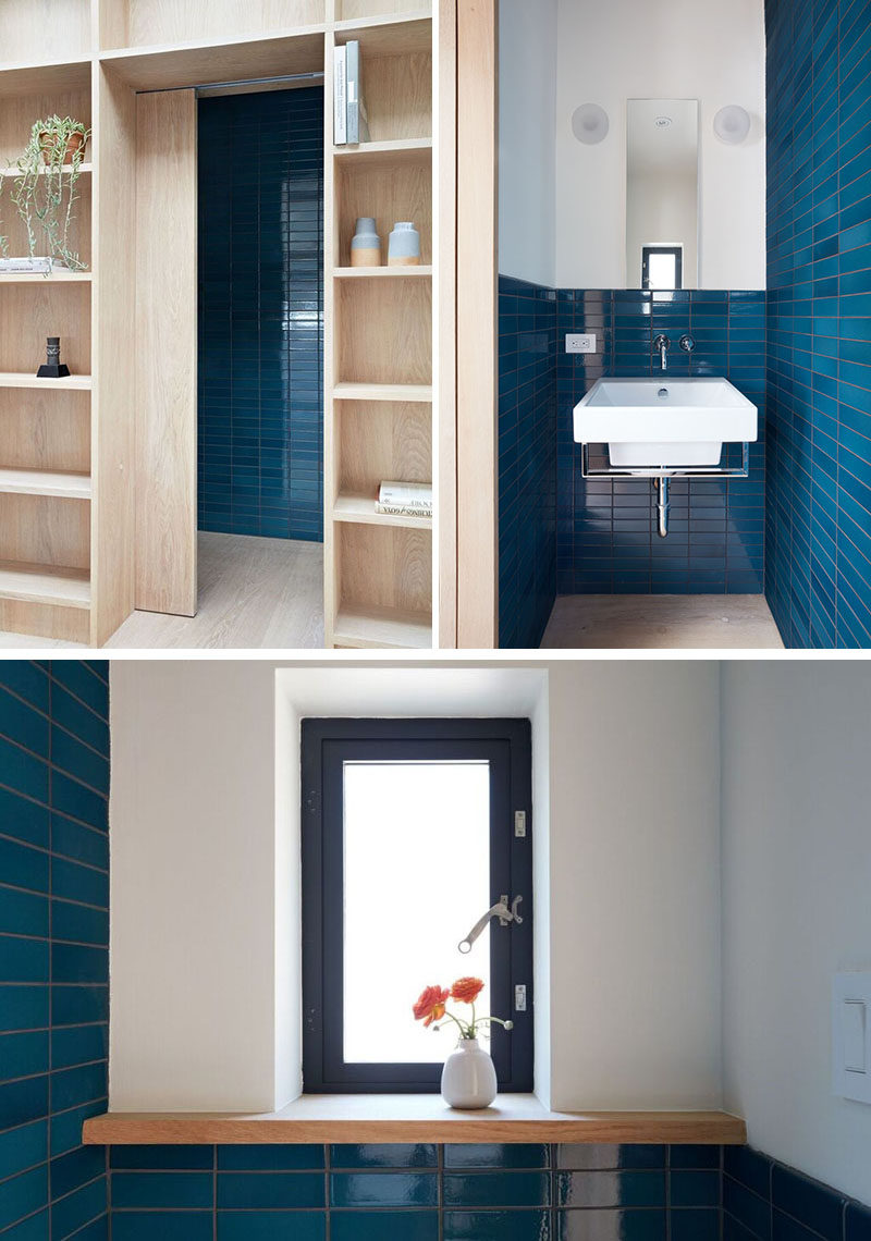Hidden within the wall of shelves in this modern backyard studio, is a door that opens to reveal a powder room, that features bold blue tiles.
