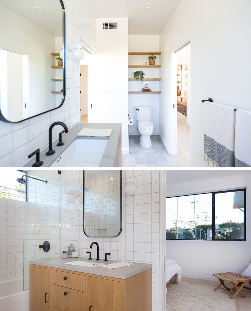 This modern jack and jill bathroom features open wood shelving above the toilet, white black hardware and faucets contrast the square white tiles.