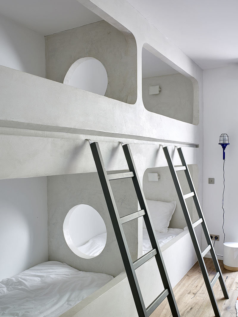 In this modern bedroom in a holiday house, a set of two bunk beds have been custom built into the design of the room. The center wall that separates the bunks has a round hole so that people can easily see and talk to each other.