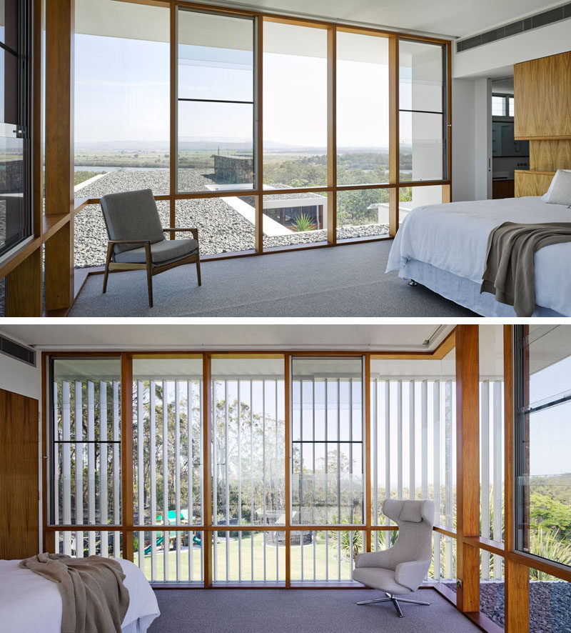 In this modern bedroom, the wood framed windows flood the room with natural light, frame the view and compliment the wood headboard.