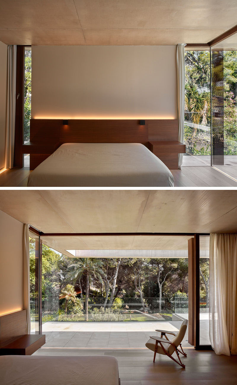 In this modern bedroom, the headboard has hidden lighting, while floor-to-ceiling windows and doors open up to the backyard.