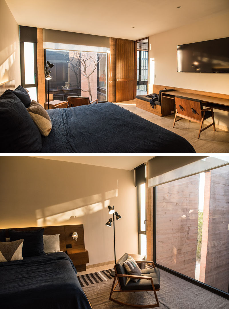 This modern bedroom has a built-in wood bench and desk, and large windows provide views of the courtyard below.