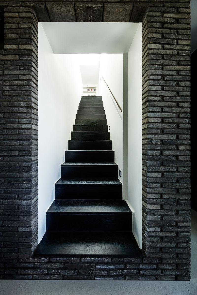 The stairs that lead up to the upper sections of this modern house have a monochrome appearance, with black stairs surrounded by white walls.