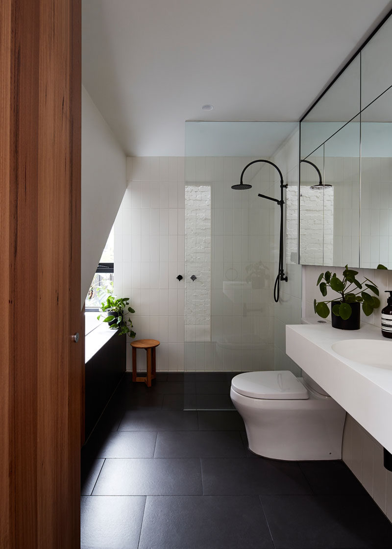 In this modern bathroom, simple white walls and tiles are paired with black floor tiles and a floating vanity.
