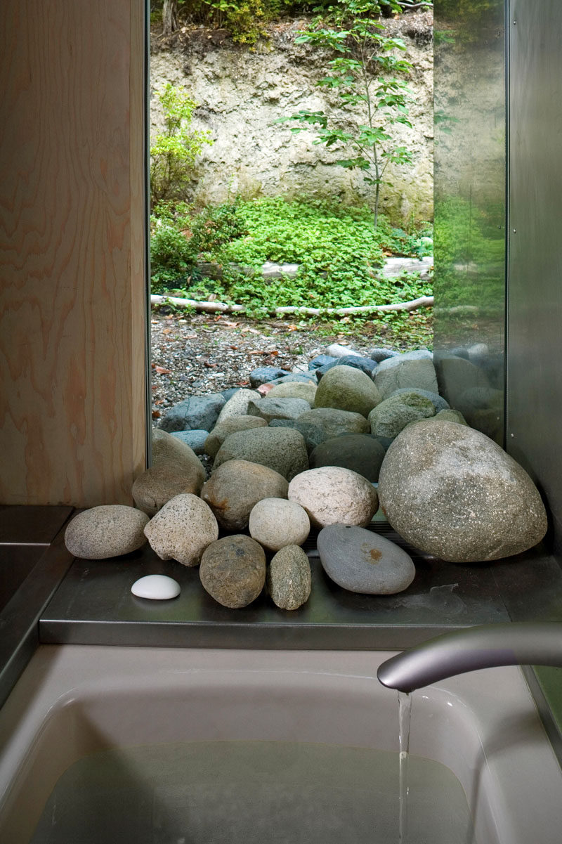 In this modern cabin bathroom, a window allows the stones appear to flow from the forest straight into the bathroom.