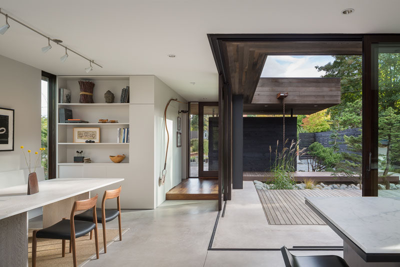 The dining room in this modern house opens up to a small courtyard surrounded by landscaping.