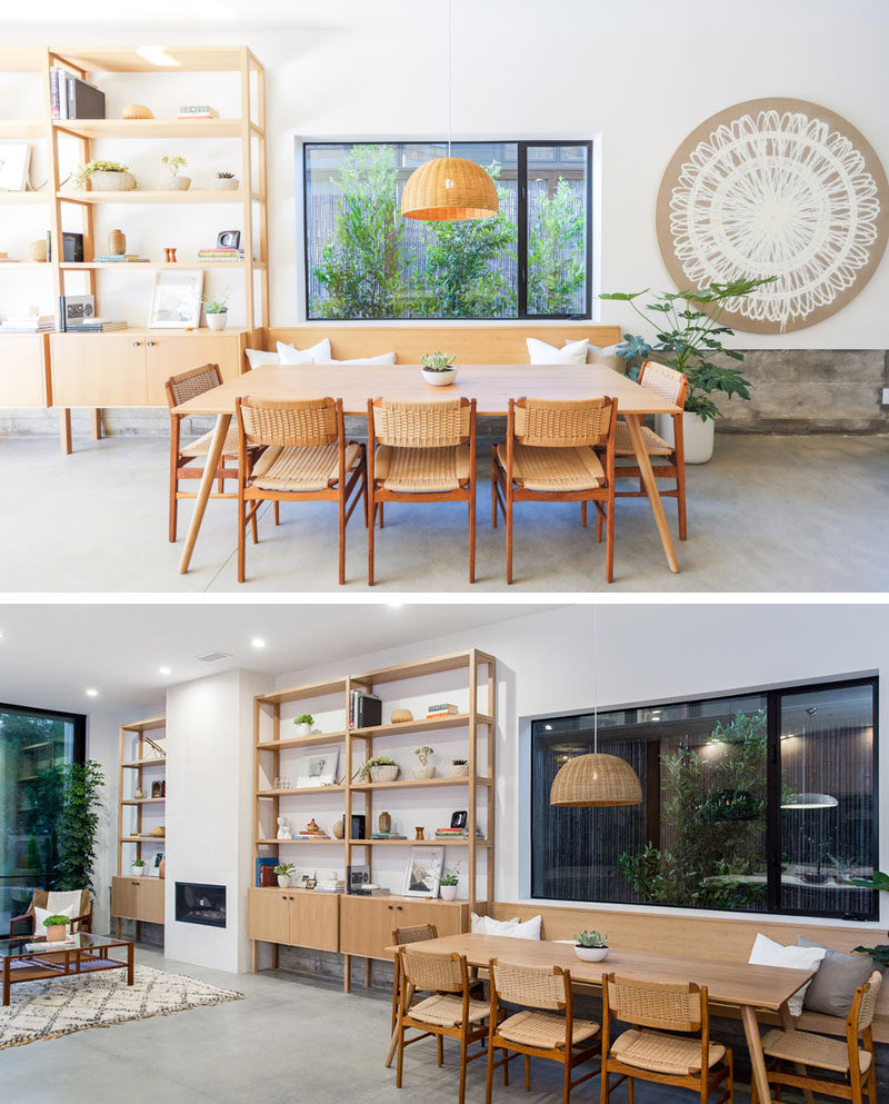 This custom wood shelving unit continues to become a bench that provides seating for the dining table. The floor throughout the main level of this modern house is concrete.