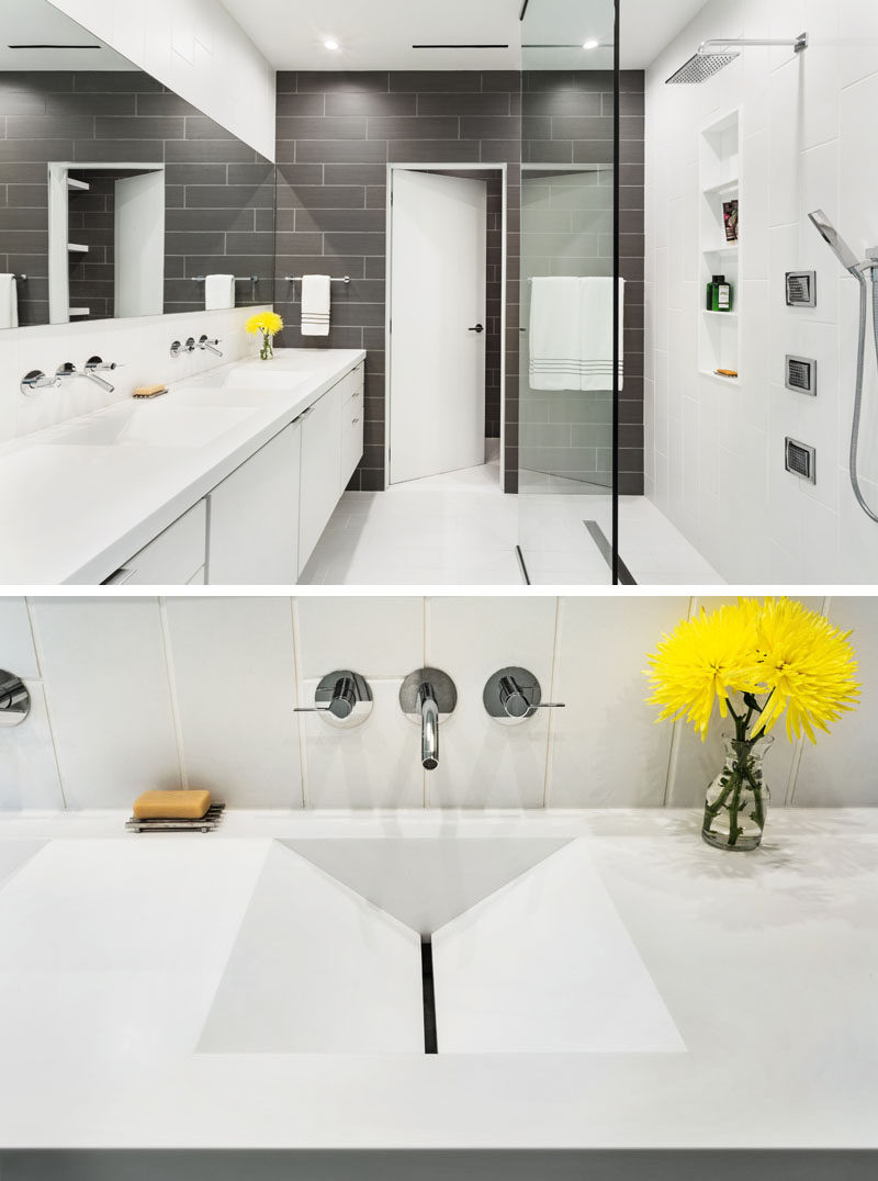 In this modern master bathroom, grey tiles have been used to create an accent wall, while a long vanity has dual sinks with an interesting design.