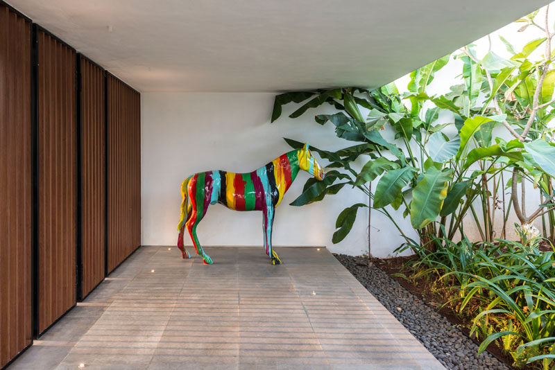 A horse sculpture adds a pop of color to this modern house.