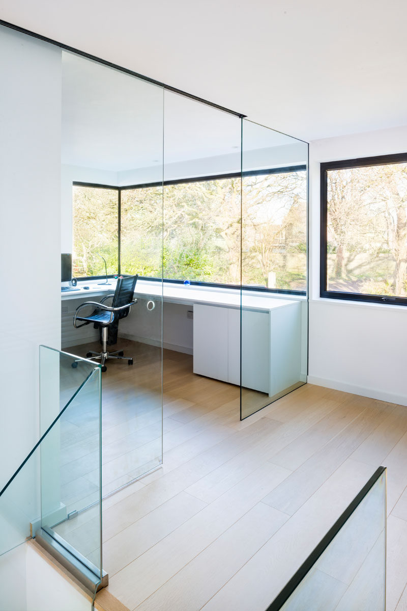 At the top of the stairs in this modern house is a home office with a glass wall and windows that look out to the surrounding landscape.