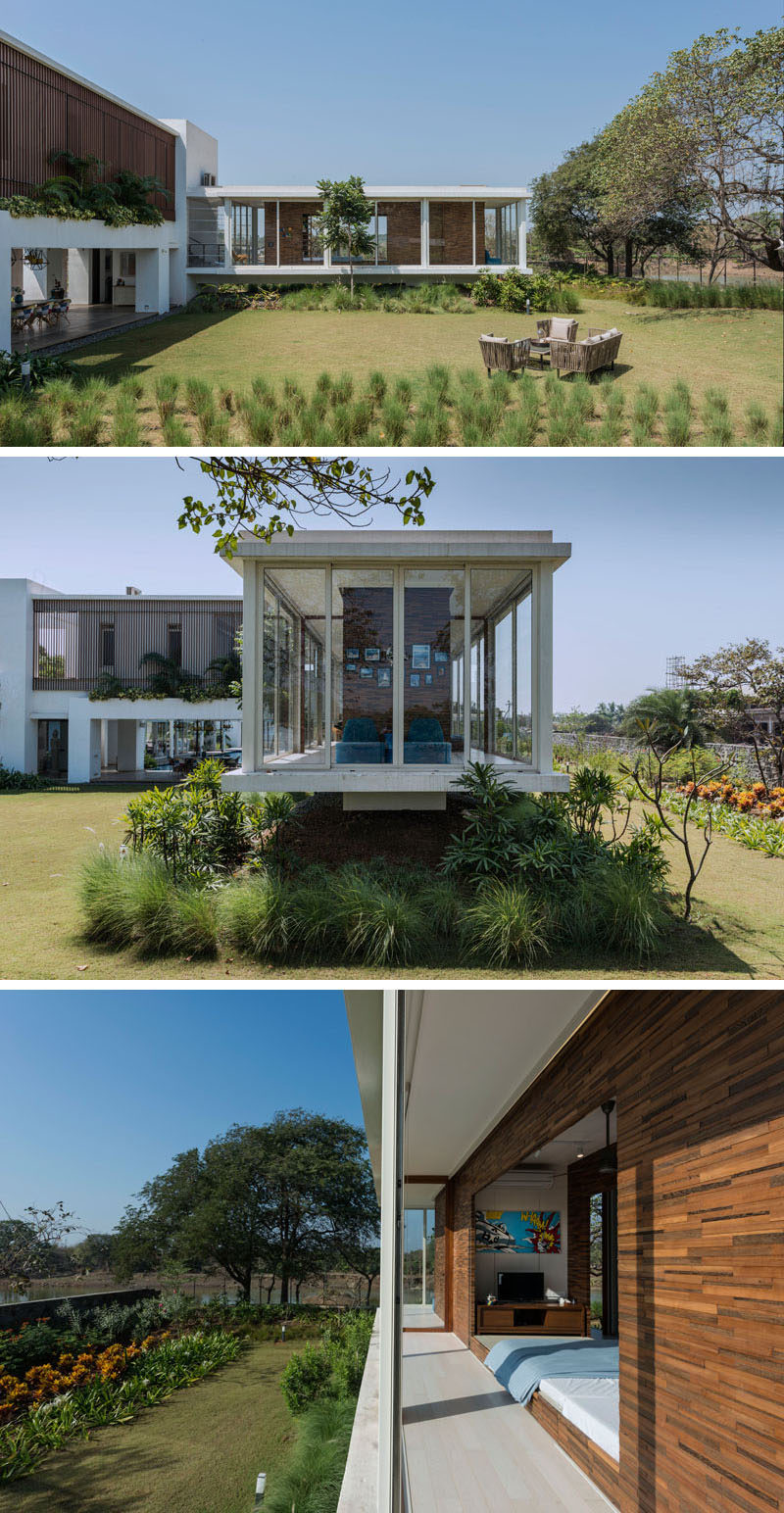For the children that live in this modern house, there's a special area just for them, a cantilevered room that features a wood box within a glass box. This cantilevered space has large floor-to-ceiling windows that look out onto the garden.