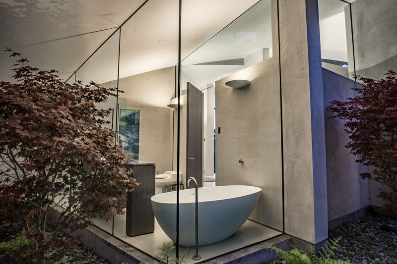 In this modern bathroom, concrete walls have been paired with tall floor-to-ceiling glass walls that provide the freestanding white bathtub with garden views.