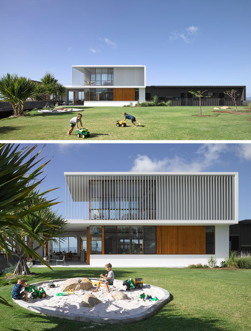 The landscaped yard of this modern house has a built-in sandbox play area.